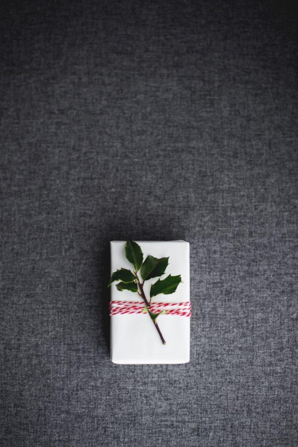 Schnelle Nummer für Last-Minute-Einpacker: Geschenk in weißes Papier (z.B. aus dem Drucker) einwicklen, rot weißes Band drumerhum wickeln und mit einem Zweig schmücken: schlicht und schön gehts dann ab unter dem Baum.